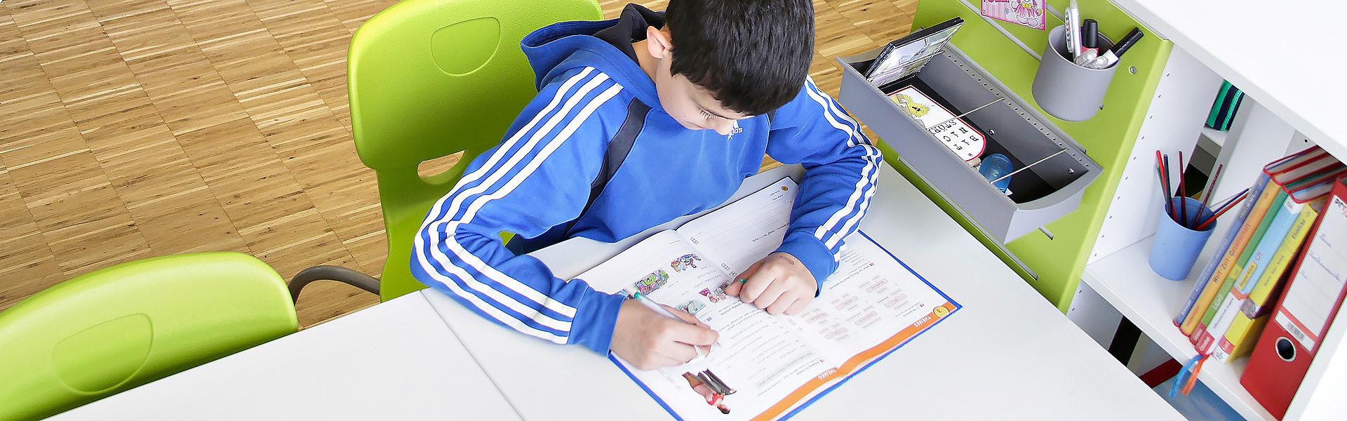 мальчик учится сидя за столом