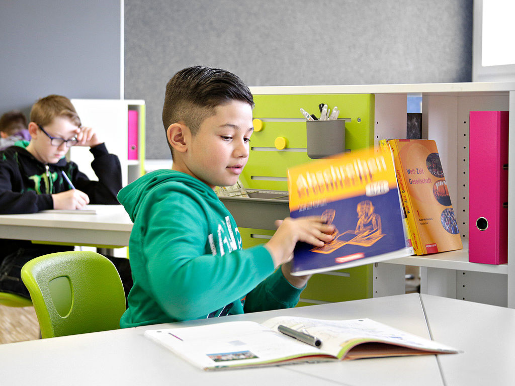 мальчик кладет учебник на стол